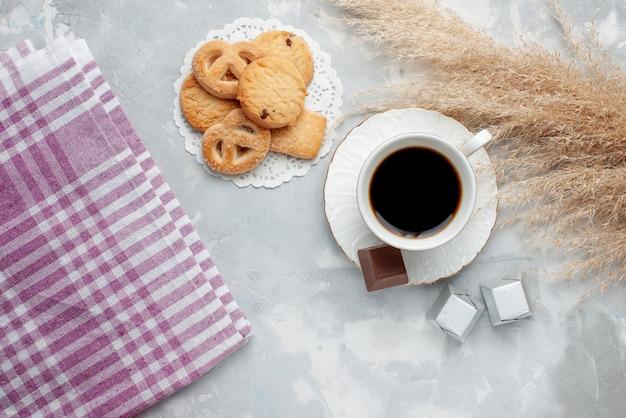 Bovenaanzicht van kopje thee met heerlijke kleine koekjes chocolade snoepjes op licht, cookie biscuit zoete thee suiker