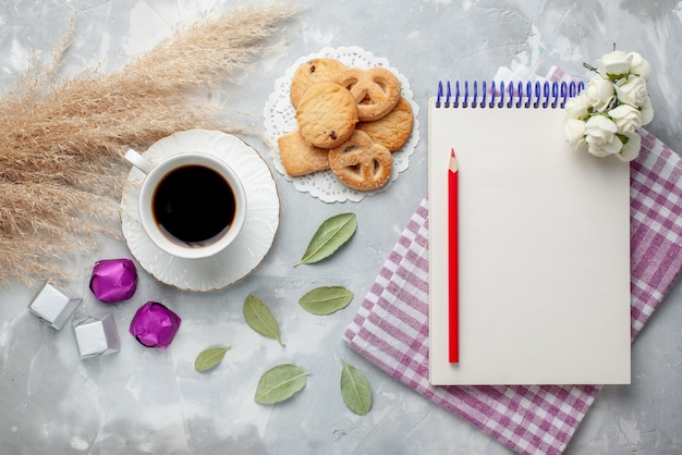 Bovenaanzicht van kopje thee met heerlijke kleine koekjes chocolade snoepjes op lichtgrijs, koekjes koekjes zoete thee suiker