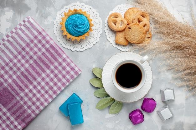 Bovenaanzicht van kopje thee met heerlijke kleine koekjes chocolade snoepjes op witte vloer, cookie biscuit candy chocoalte