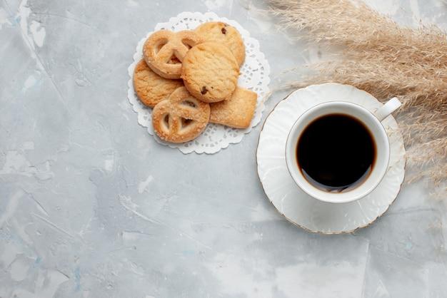 Bovenaanzicht van kopje thee met heerlijke kleine koekjes op licht bureau, koekjes koekjes zoete thee suiker