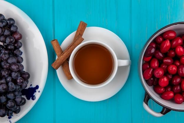 Bovenaanzicht van kopje thee met kaneel op schotel en plaat van druivenkom cornel bessen op blauwe achtergrond
