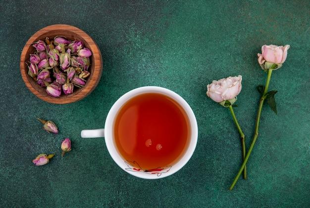 Bovenaanzicht van kopje thee met licht roze rozen en gedroogde rozenknoppen in een kom op een groen oppervlak