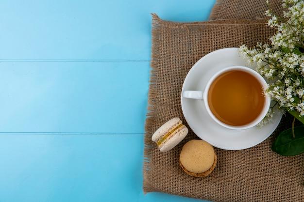 Bovenaanzicht van kopje thee met macarons en bloemen op een beige servet op een blauwe ondergrond