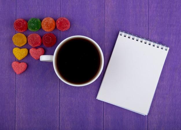 Bovenaanzicht van kopje thee met marmelads en notitieblok op paarse achtergrond