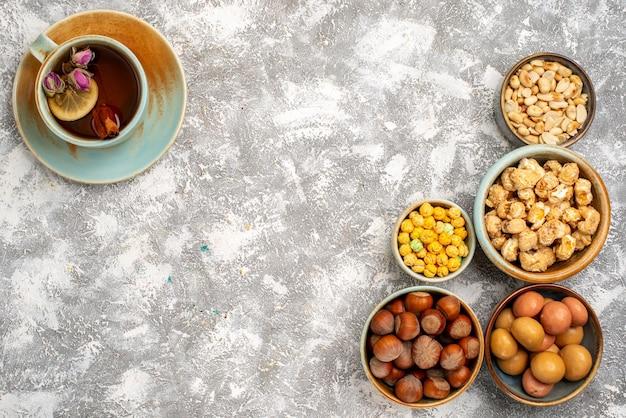 Bovenaanzicht van kopje thee met noten en snoepjes op witte ondergrond