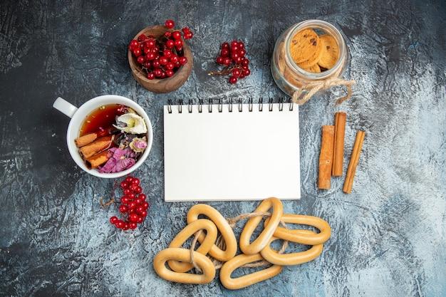 Bovenaanzicht van kopje thee met rode veenbessen en crackers op donkere ondergrond Gratis Foto