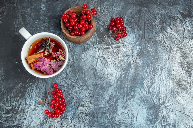 Bovenaanzicht van kopje thee met rode veenbessen op donkere ondergrond