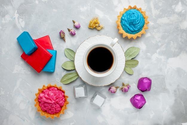 Bovenaanzicht van kopje thee met roze crème taart chocolade snoepjes op licht bureau, koekje zoete thee snoep