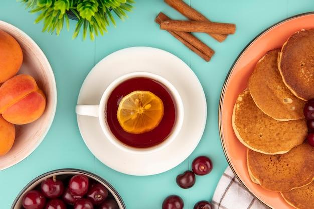 Bovenaanzicht van kopje thee met schijfje citroen erin en plaat van pannenkoeken met abrikozen en kersen en kaneel op blauwe achtergrond
