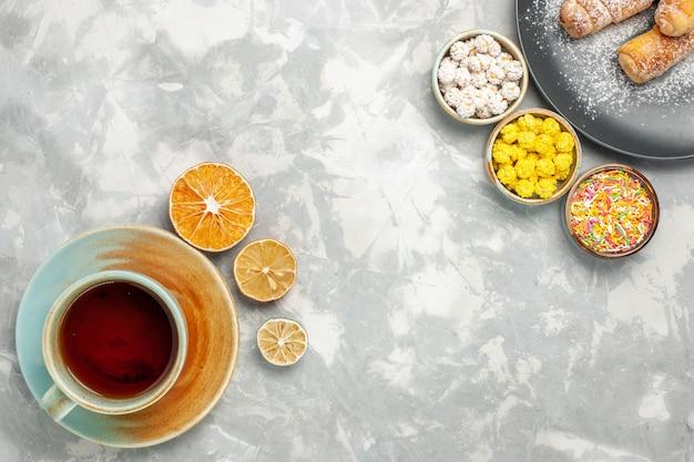 Bovenaanzicht van kopje thee met snoepjes en bagels op witte ondergrond