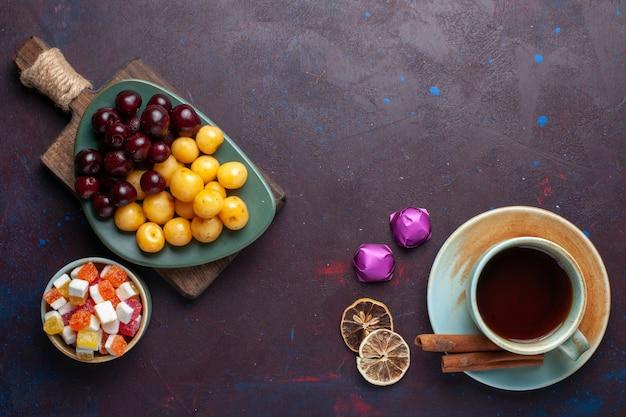 Bovenaanzicht van kopje thee met snoepjes, kersen en kaneel op donkere ondergrond