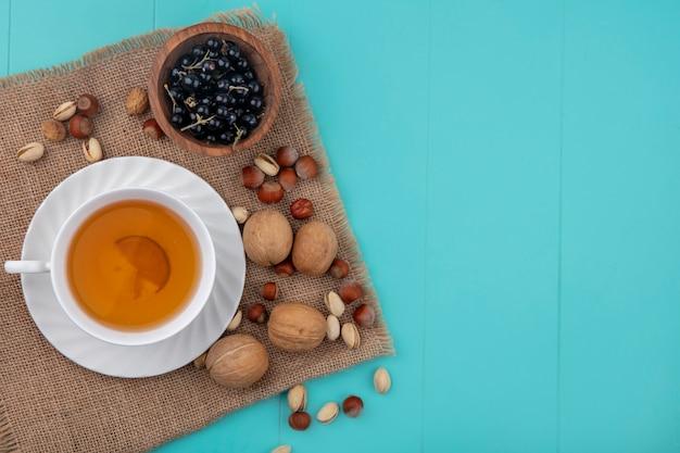 Bovenaanzicht van kopje thee met walnoten, hazelnoten met pistachenoten en zwarte bessen op een beige servet op een turquoise ondergrond