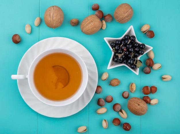 Bovenaanzicht van kopje thee met walnoten, hazelnoten met pistachenoten en zwarte bessen op een turkoois oppervlak