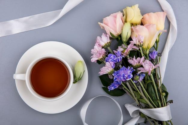 Bovenaanzicht van kopje thee op schotel en bloemen met lint op grijze achtergrond