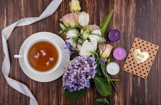 Bovenaanzicht van kopje thee op schotel en bloemen met mis je kaart lint en kaarsen op houten achtergrond