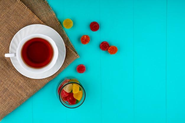 Bovenaanzicht van kopje thee op schotel op zak en marmelads in kom en op blauwe achtergrond met kopie ruimte