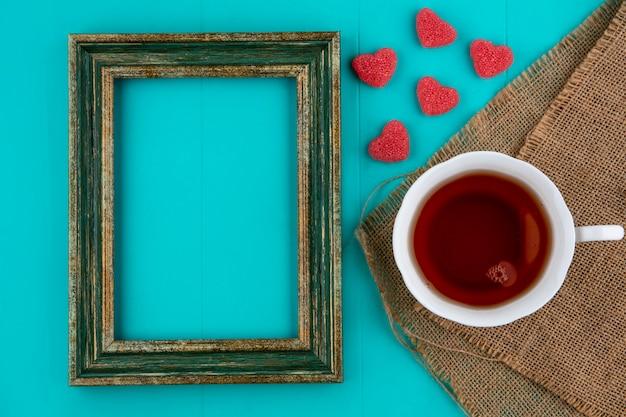 Bovenaanzicht van kopje thee op zak met marmelads en frame op blauwe achtergrond met kopie ruimte