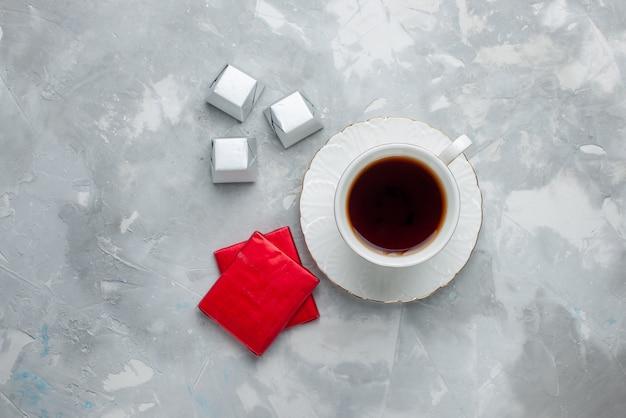 Bovenaanzicht van kopje thee warm binnen witte kop op glazen plaat met zilveren pakket chocolade snoepjes op licht bureau, thee drink zoete chocolade