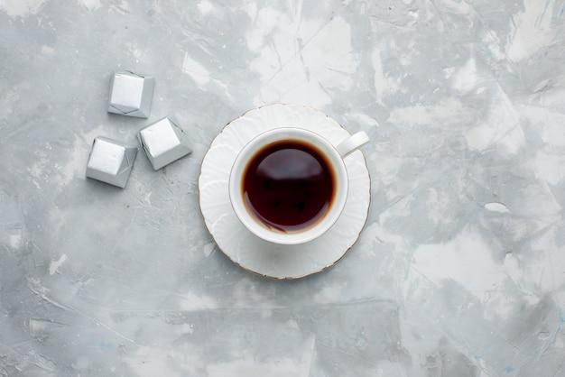 Bovenaanzicht van kopje thee warm binnen witte kop op glazen plaat met zilveren pakket snoepjes op licht bureau, thee drinken zoete chocoladekoekje