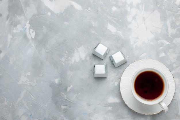 Bovenaanzicht van kopje thee warm in witte kop op glazen plaat met zilveren pakket chocolade snoepjes op licht bureau, drink zoete chocoladekoekje