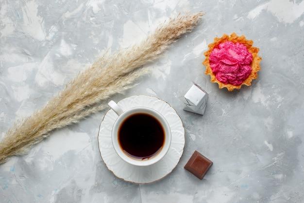 Bovenaanzicht van kopje thee warm met chocolade en cake op wit bureau, koekjes snoep chocoladethee
