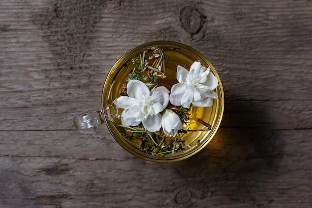 Bovenaanzicht van kopje warme groene thee met jasmijn bloemen