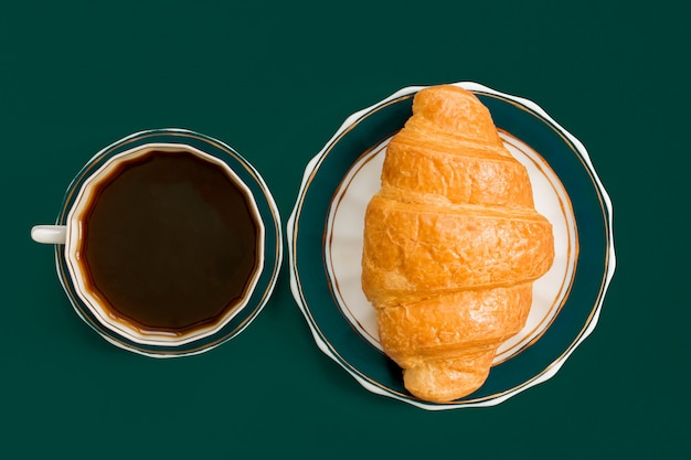 Bovenaanzicht van kopje zwarte koffie en croissant op een bord. ochtendontbijt in franse stijl.