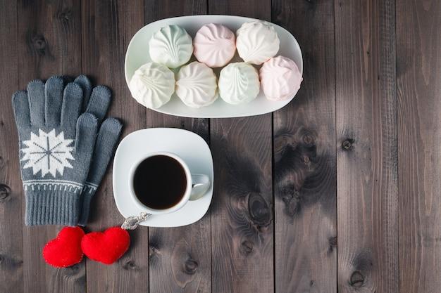 Bovenaanzicht van kopje zwarte koffie met handschoenen op houten achtergrond