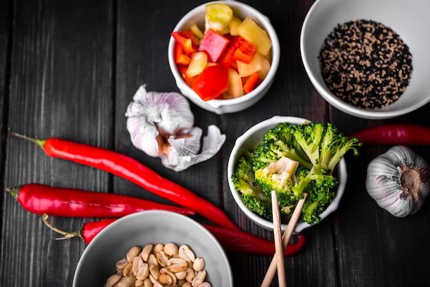 Bovenaanzicht van kopjes groenten en pinda's