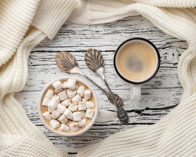 Bovenaanzicht van kopjes koffie en warme chocolademelk met marshmallows