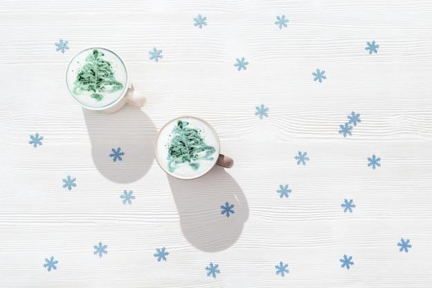Bovenaanzicht van kopjes koffie met kerstboom