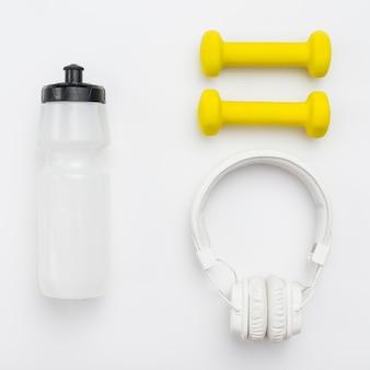 Bovenaanzicht van koptelefoon met fles water en gewichten