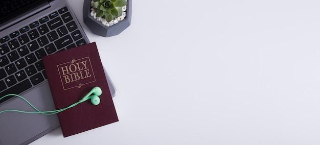 Bovenaanzicht van koptelefoon op laptop en bijbel