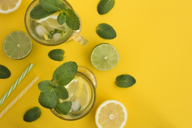 Bovenaanzicht van koude limonade met citroen en munt op het gele oppervlak