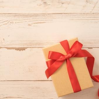 Bovenaanzicht van kraft geschenkdoos met rode strik voor valentijnsdag.