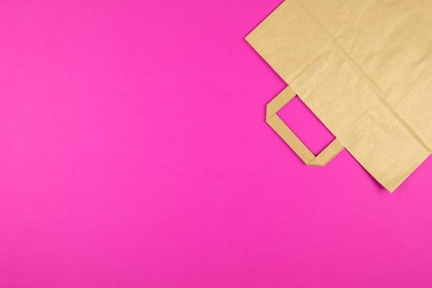 Bovenaanzicht van kraft papieren zak op roze achtergrond.