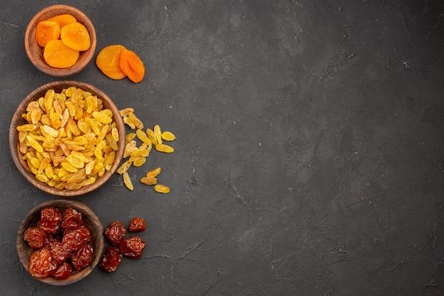 Bovenaanzicht van krenten en rozijnen met gedroogde abrikozen in kleine potten op grijs oppervlak