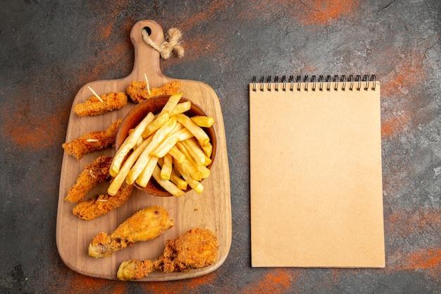 Bovenaanzicht van krokant gebakken aardappel en kip op de houten snijplank