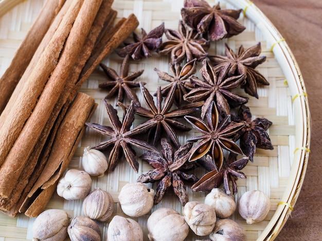 Bovenaanzicht van kruiden en specerijen in traditionele geweven bamboe mand op houten tafel.