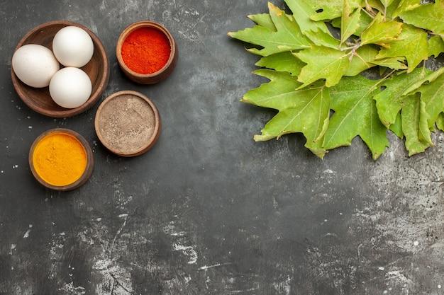 Bovenaanzicht van kruiden kom met eieren en bladeren aan de bovenzijde op donkergrijze tafel