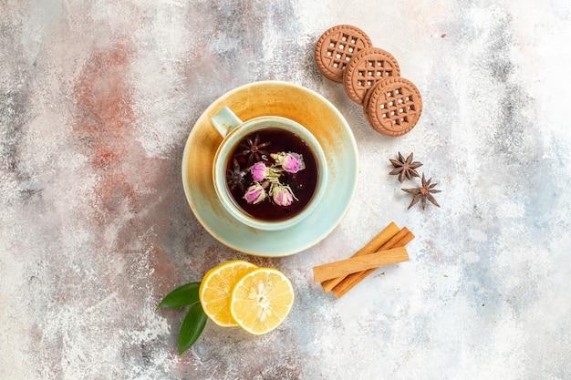 Bovenaanzicht van kruidenthee koekjes en kaneel limoen citroen plakjes op witte achtergrond