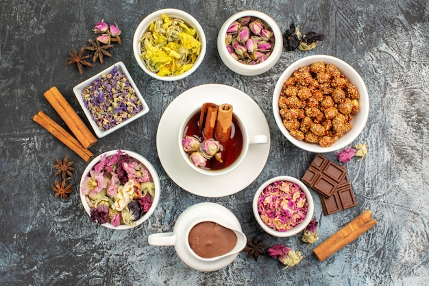 Bovenaanzicht van kruidenthee met droge bloemen en chocolade en noten op grijze grond