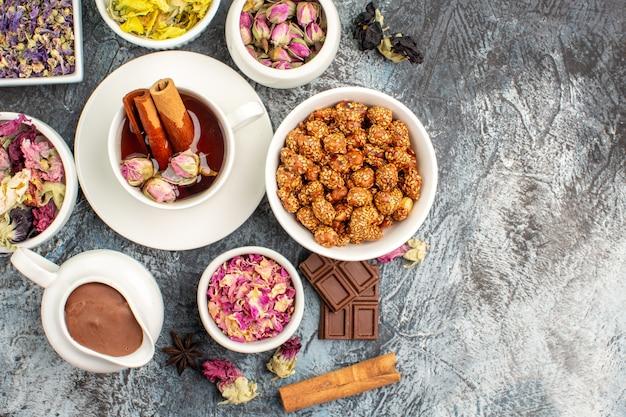 Bovenaanzicht van kruidenthee met een kom met noten en chocolade en verschillende soorten bloemen op grijze grond