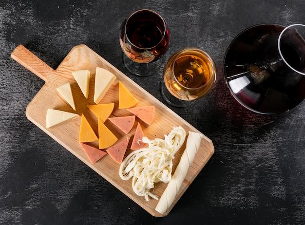 Bovenaanzicht van kruik met wijn en kaas op houten snijplank op donkere horizontaal