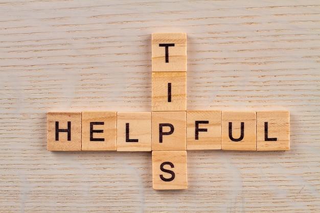 Bovenaanzicht van kruiswoordraadsel met nuttige tips voor woorden. alfabetblokken met letters op het houten bord.
