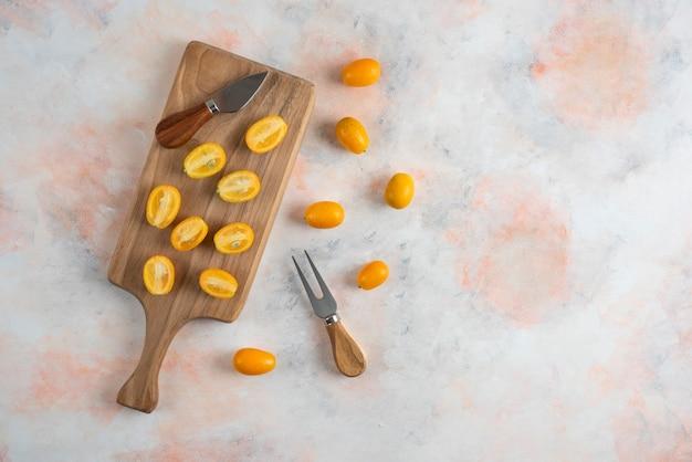 Bovenaanzicht van kumquats geheel of half gesneden op een houten bord
