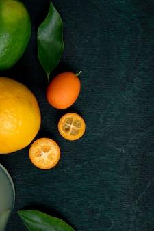 Bovenaanzicht van kumquats met citroen en limoen versierd met bladeren op groene ondergrond