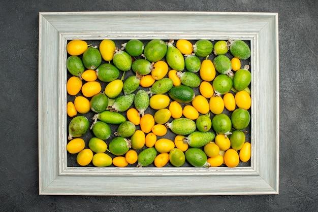 Bovenaanzicht van kumquats op grijze fotolijst op een zwarte achtergrond