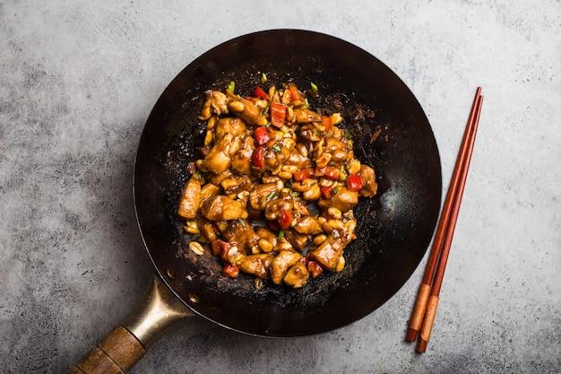 Bovenaanzicht van kung pao-kip, geroerbakt chinees traditioneel gerecht met kip, pinda's, groenten, chilipepers in een wokpan. chinees diner, rustieke betonnen achtergrond