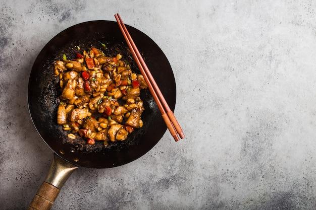 Bovenaanzicht van kung pao-kip, geroerbakt chinees traditioneel gerecht met kip, pinda's, groenten, chilipepers in een wokpan, ruimte voor tekst. chinees diner, eetstokjes, rustieke betonnen achtergrond